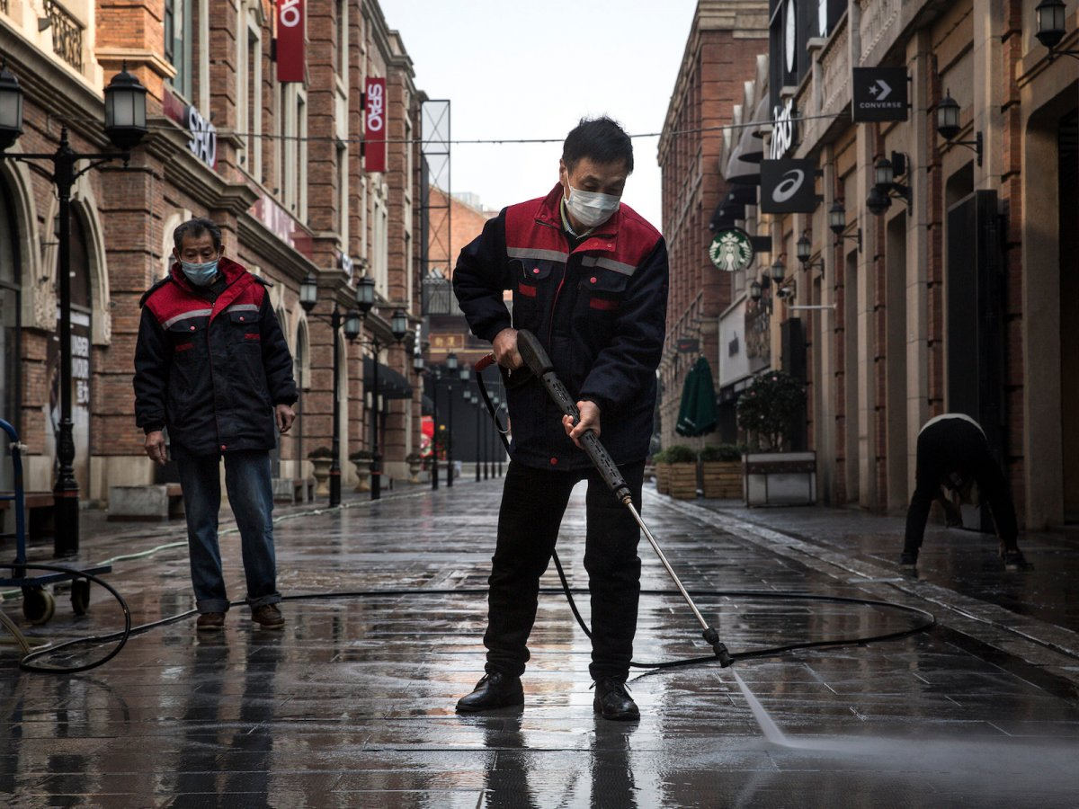 Cleaners wash a street with a high-pressure water gun, 3 February 2020, Wuhan, China. (Getty Images)