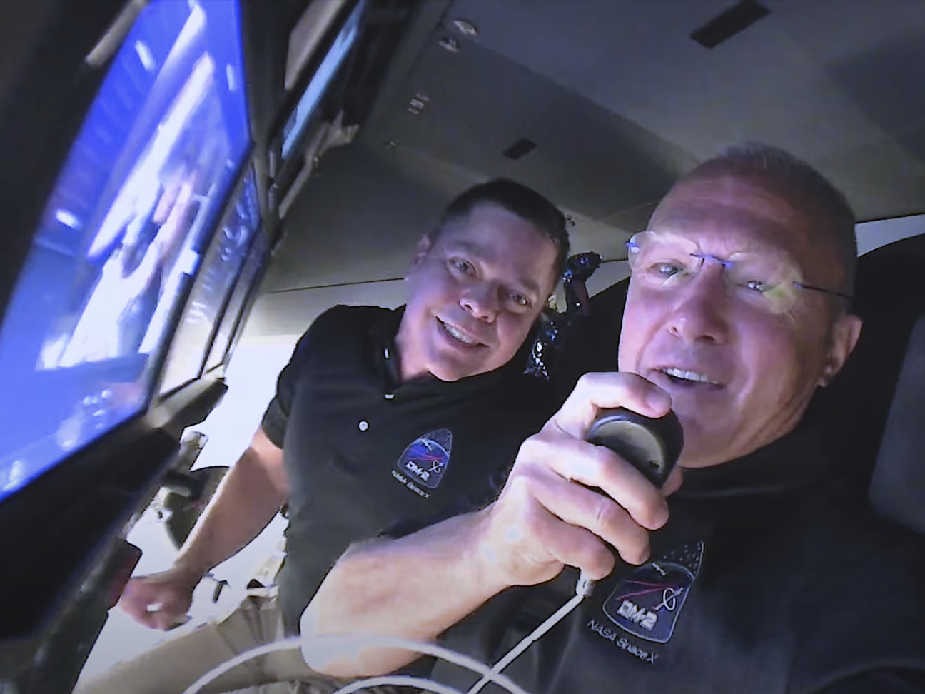 Bob Behnken (left) and Doug Hurley wish their families goodnight from inside the Crew Dragon capsule, May 30, 2020. (SpaceX)