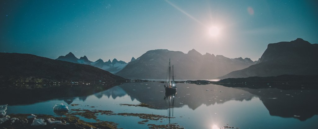 A moonlit sailboat on East Greenland's icy fjords.