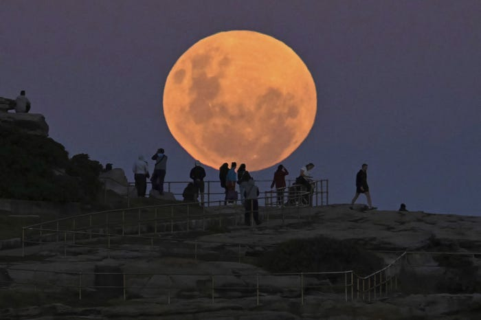 close up of pink full moon with silhouettes of people on a cliff