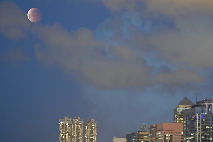 Half eclipsed moon in blue sky with low cloud cover, over a city skyline