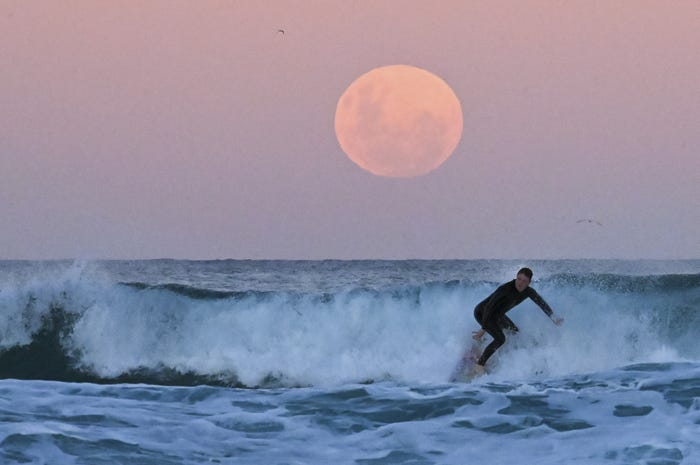 Close up of pink tinged moon at dusk near an ocean horizon with a surfer in the foreground