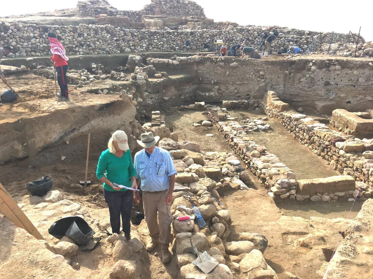 Researchers near the ruins, with the destruction layer about midway down each exposed wall. (Phil Silvia, CC BY-ND)