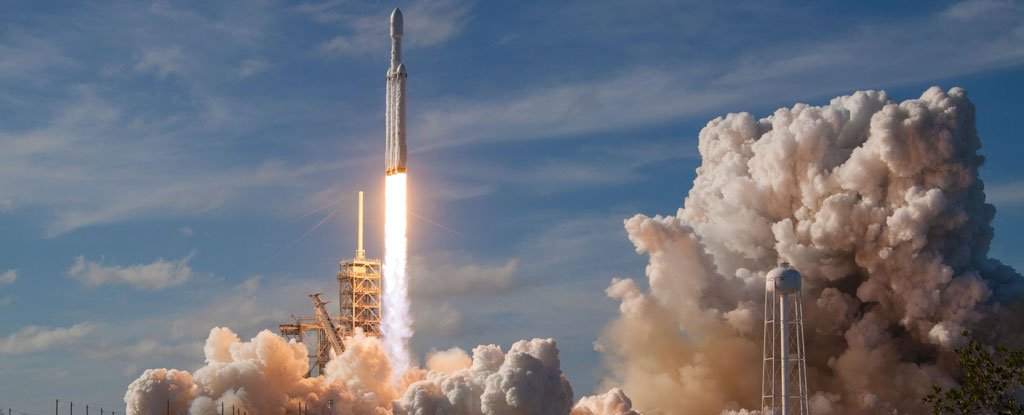 A SpaceX Falcon Heavy lifts off from a launchpad.